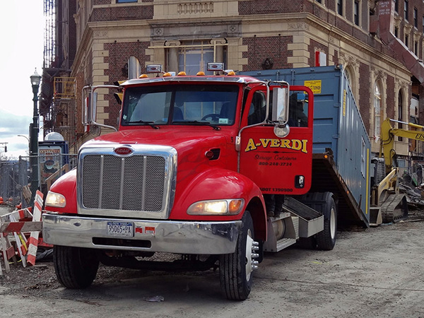 Rollback Truck Delivering Shipping Container to Construction Jobsite
